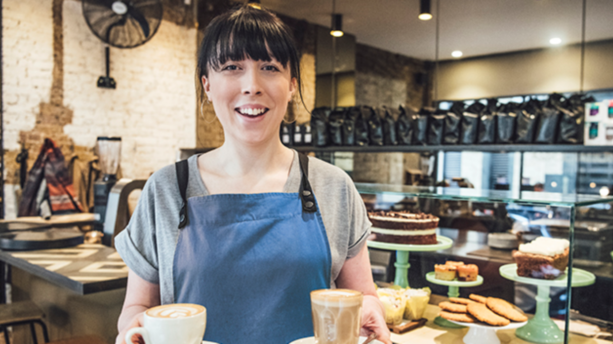 Female barista in her 20s serving coffee in cafe with cakes on display in background