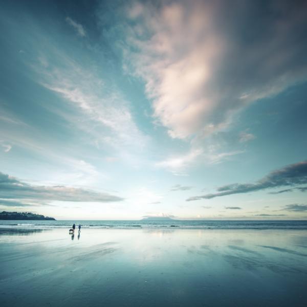 Two people walking across a beach
