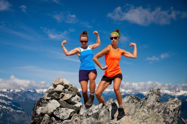 Two women pose with arm muscles flexed on top of a mountain