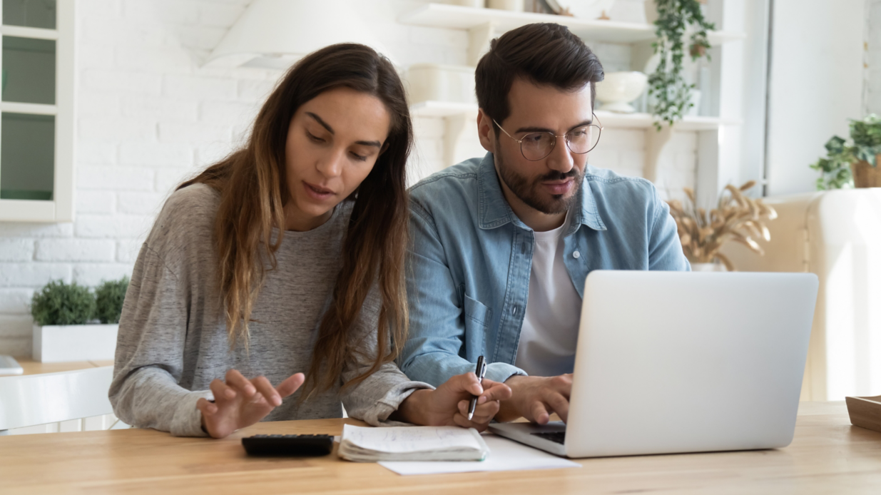 Serious man and woman calculating bills, using calculator and laptop, online banking services, family discussing and planning budget, focused wife and husband checking finances together