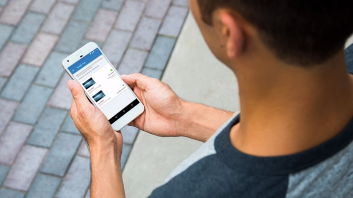 A man holding a mobile device with ANZ goMoney displaying
