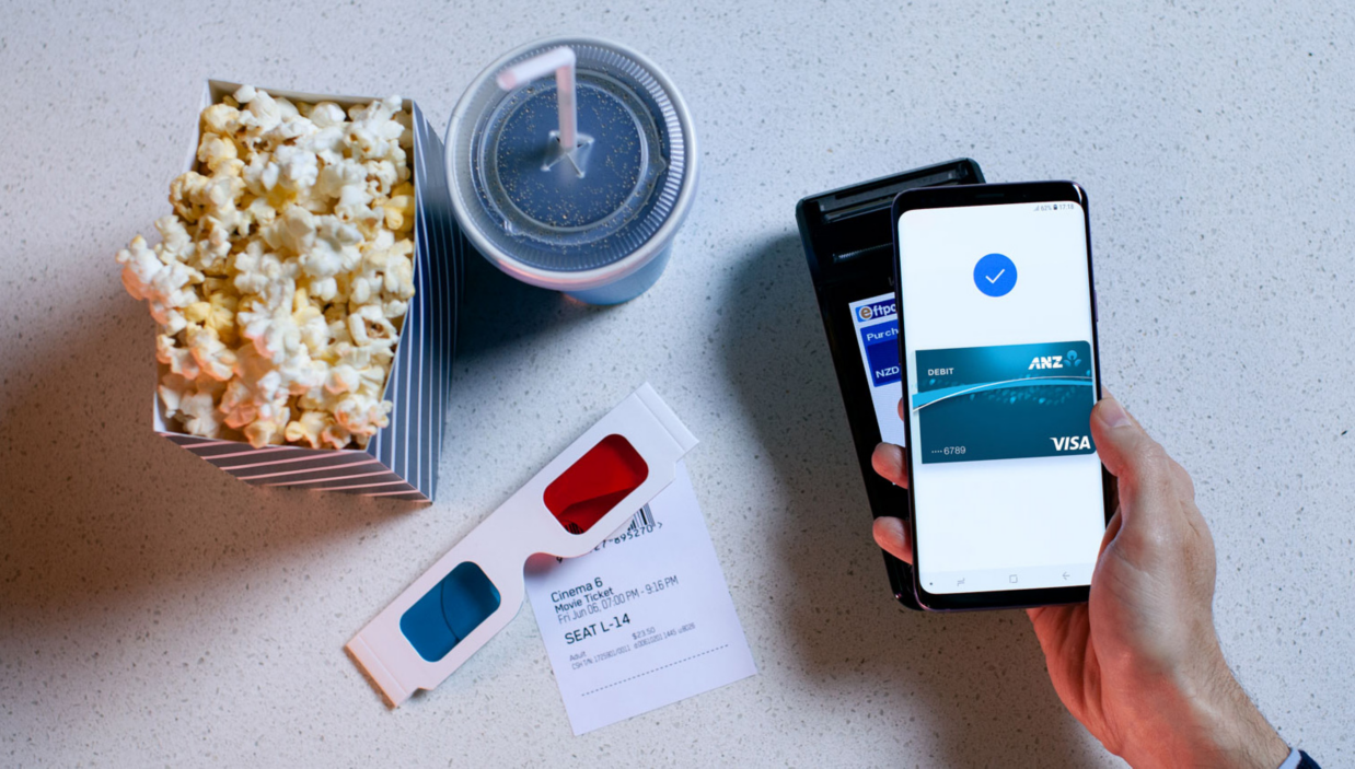 A mobile phone being used to pay for popcorn and a drink
